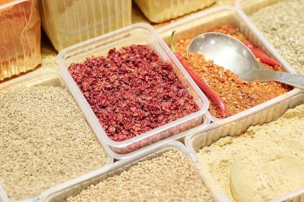 Close-up de diversas especias en recipientes desechables utilizados para cocinar platos salados en el mercado de alimentos