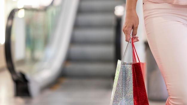 Close-up elegante mujer llevando bolsas de compras