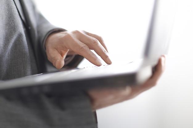 Close up.empresario escribiendo en un teclado portátil.aislado sobre fondo blanco.