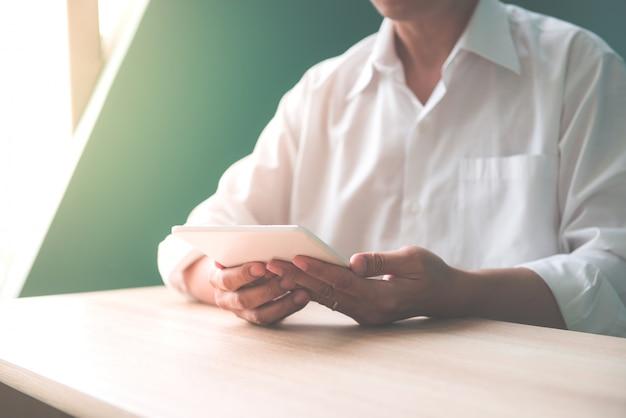 Close-up de empresario sonriente feliz o empleador trabajando en tableta digital y hablando por su teléfono inteligente en el interior de la oficina moderna, luz de bengala, imágenes de estilo efecto vintage.