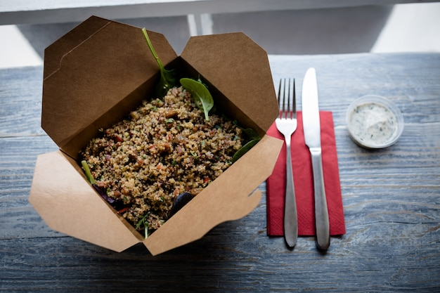 Close-up de ensalada con tenedor y cuchillo en la mesa