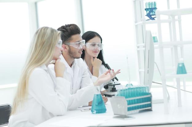 Close up.un equipo de científicos discutiendo algo en el escritorio