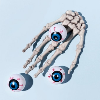 Close-up espeluznante mano de esqueleto de halloween con globos oculares