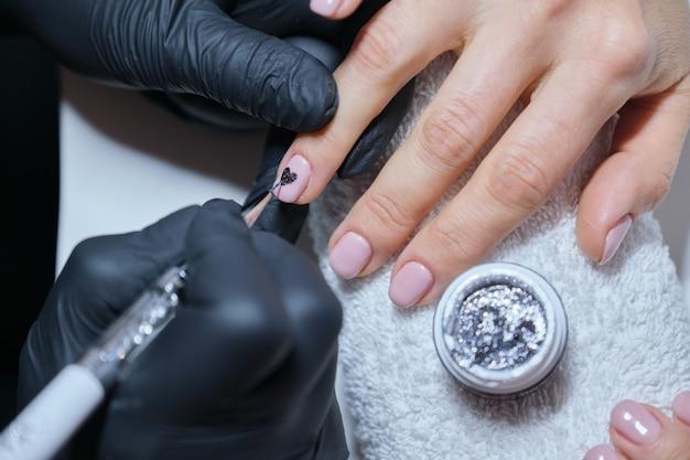 Close-up esteticista pintura diseño de arte en las uñas.