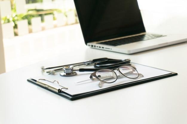 Close-up de estetoscopio, papel, portátil en mesa de médico. enfoque selectivo.