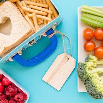 Close-up etiquetado lunchbox cerca de los alimentos