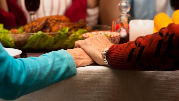 Close-up familia cogidos de la mano en el evento de acción de gracias