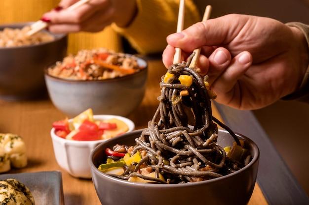 Close-up de fideos en un tazón con otra comida asiática