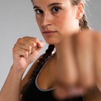 Close-up fit mujer en posición de combate con mano borrosa