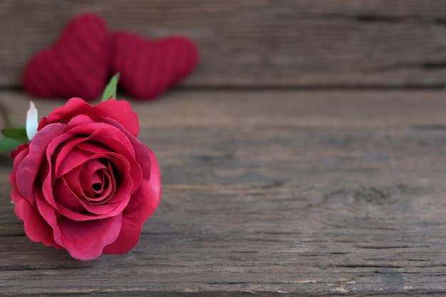 Close up de flor rosa roja en la mesa de madera rústica