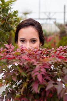Close-up fotogénica mujer escondida detrás de las plantas en invernadero