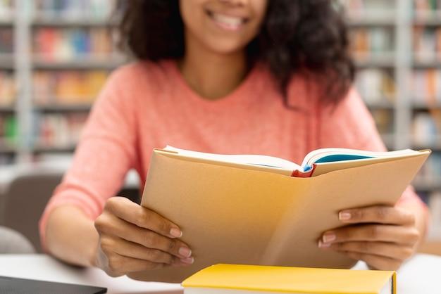 Close-up girl en la biblioteca estudiando y usando laptop