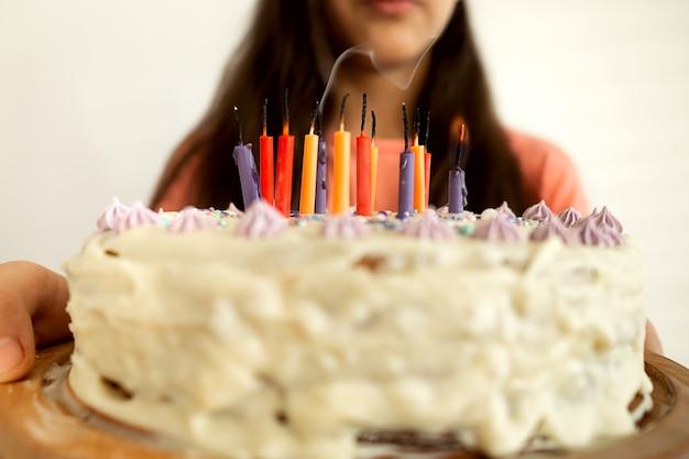 Close-up girl hads sosteniendo pastel de cumpleaños para hornear en casa con velas encendidas. agitando la fiesta de cumpleaños feliz en casa.