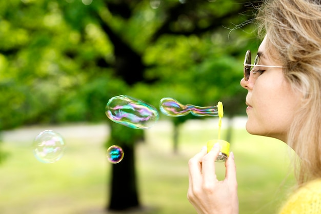 Close-up girl jugando con máquina de burbujas