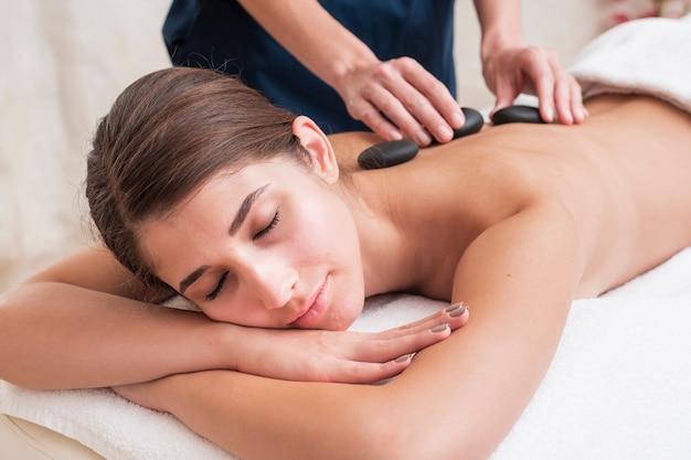 Close-up girl recibiendo tratamiento de spa de piedra