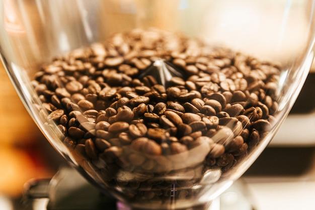 Close-up granos de café dentro de la máquina de molienda de molinillo de café eléctrico. molino de café para el hogar y la máquina de negocios.