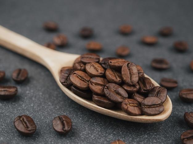 Close-up de granos de café tailandés tostados en una cuchara de madera sobre azulejos ásperos gris oscuro