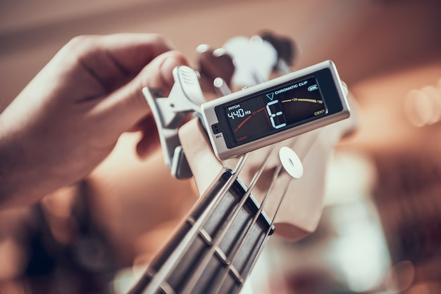 Close up guitarist tunes guitar con clip de afinador