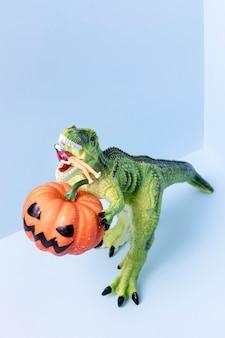 Close-up halloween dinosaurio juguete sosteniendo calabaza