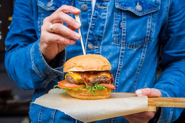 Close-up hamburguesa con carne y verduras en manos de un visitante del restaurante