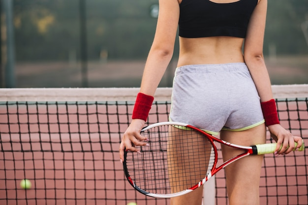 Close-up hembra joven jugando tenis en campo