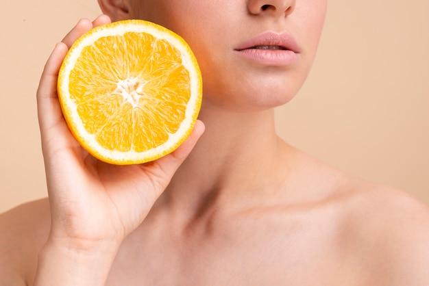Close-up hermosa modelo con media naranja