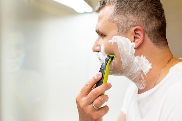 Close-up hombre afeitado en el baño