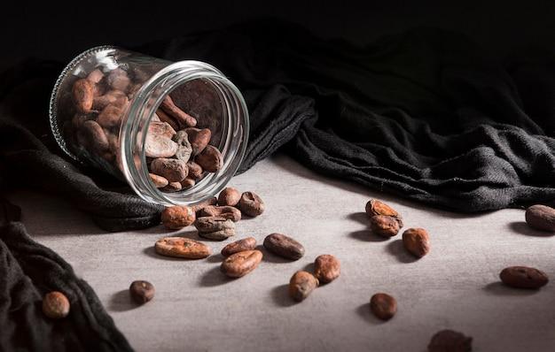 Close-up jarra derramada con granos de cacao