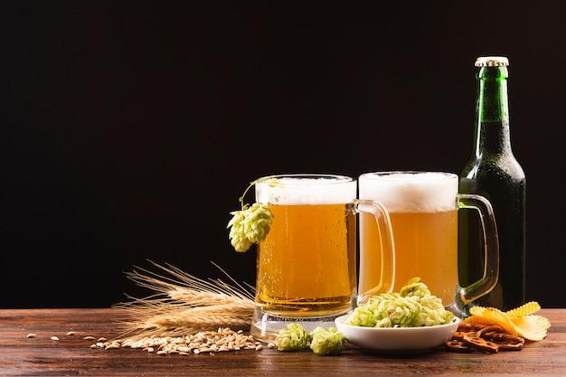 Close-up jarras de cerveza con ingredientes