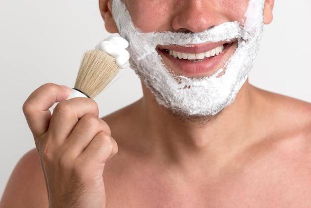 Close-up de joven aplicando espuma de afeitar con brocha en la cara