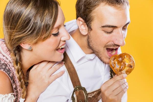 Close-up joven pareja comiendo un pretzel