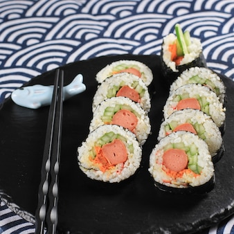 Close up korean roll gimbap (kimbob o kimbap) hecho de arroz blanco al vapor (bap) y varios otros ingredientes, como kyuri, zanahoria, salchicha, palito de cangrejo o kimchi y envuelto con algas marinas.