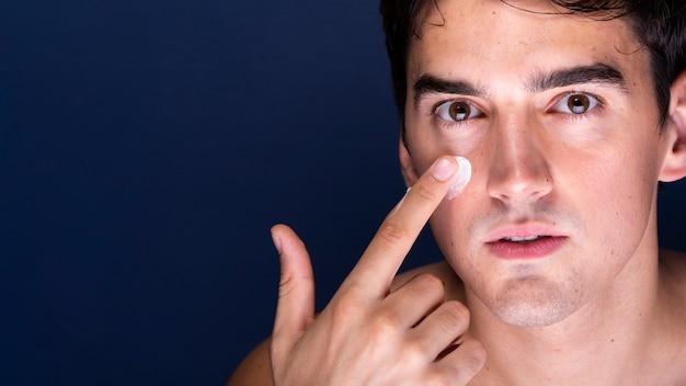 Close-up macho adulto aplicando crema