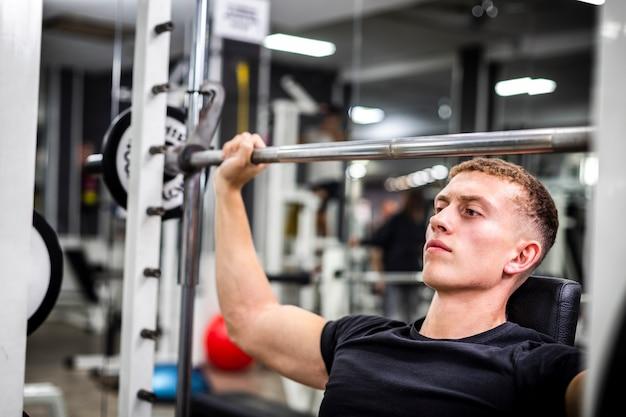 Close-up macho joven en el entrenamiento de gimnasio para brazos