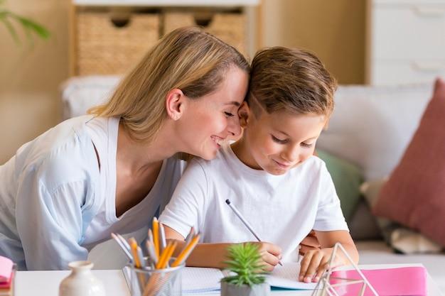 Close-up madre susurra palabras en el oído del niño
