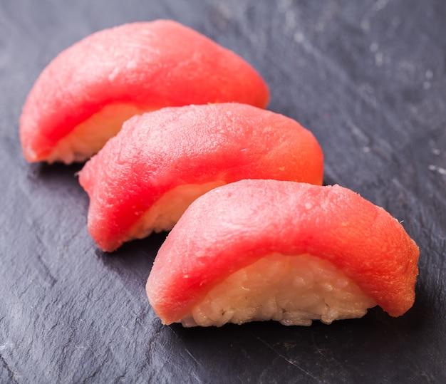 Close-up de maguro sushi con atún sobre un fondo de pizarra negra