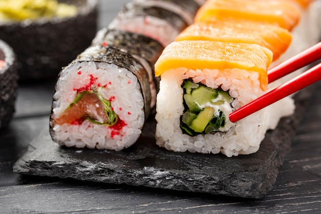 Close-up maki sushi en pizarra con palillos