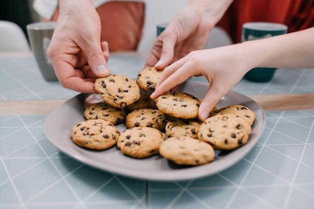 Close-up de mano agarrando galletas frescas de la placa en la mesa