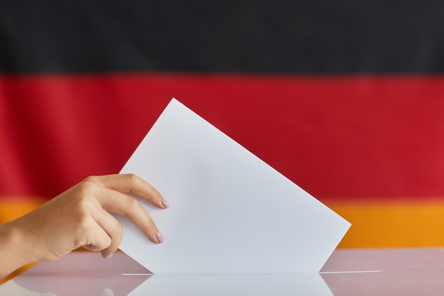 Close-up de mano femenina sosteniendo un sobre blanco y votando en la mesa de votación