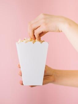 Close-up mano recogiendo palomitas de maíz de la caja