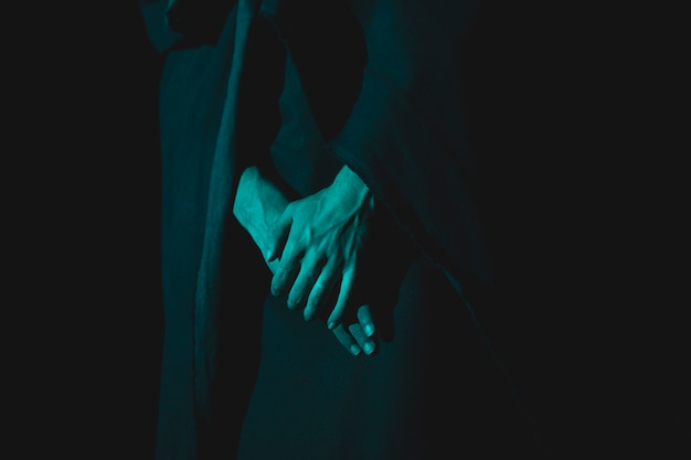 Close-up de mano sujetando juntos en la oscuridad