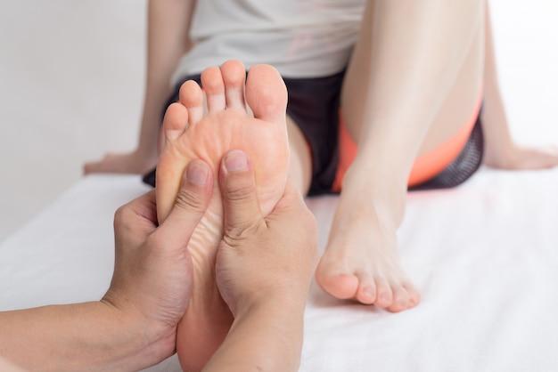 Close-up de manos femeninas haciendo masaje de pies