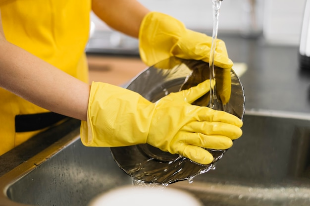 Close-up manos lavando platos