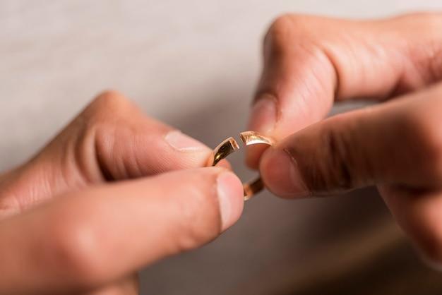 Close-up manos sosteniendo anillo roto