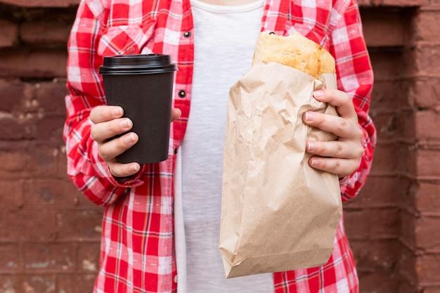 Close-up manos sosteniendo café y comida