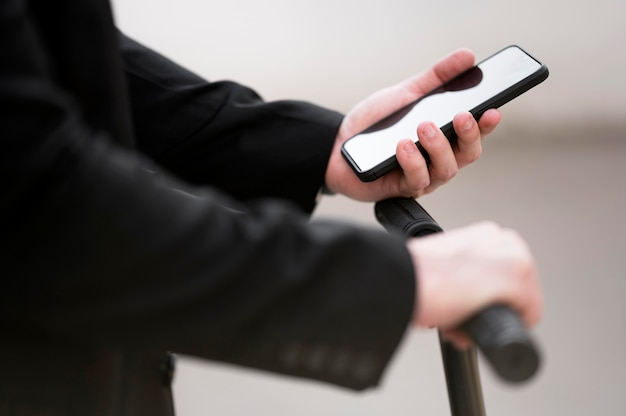 Close-up masculino usando scooter con teléfono móvil