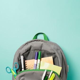 Close up mochila abierta con accesorios escolares.
