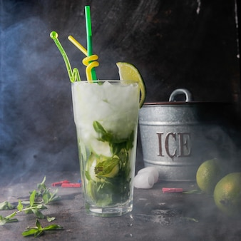 Close-up mojito cocktail con menta, lima, hielo, cubo de hielo con humo