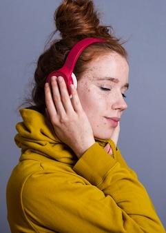 Close-up mujer bonita con auriculares y sudadera con capucha amarilla