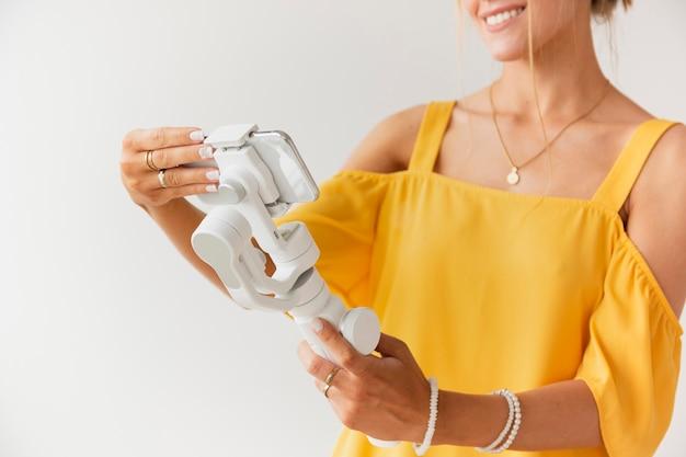 Close-up mujer configurando teléfono en soporte de filmación